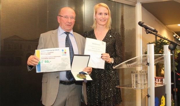 Simon van Dijk kreeg de oorkonde uitgereikt door wethouder Jeanet van der Laan.