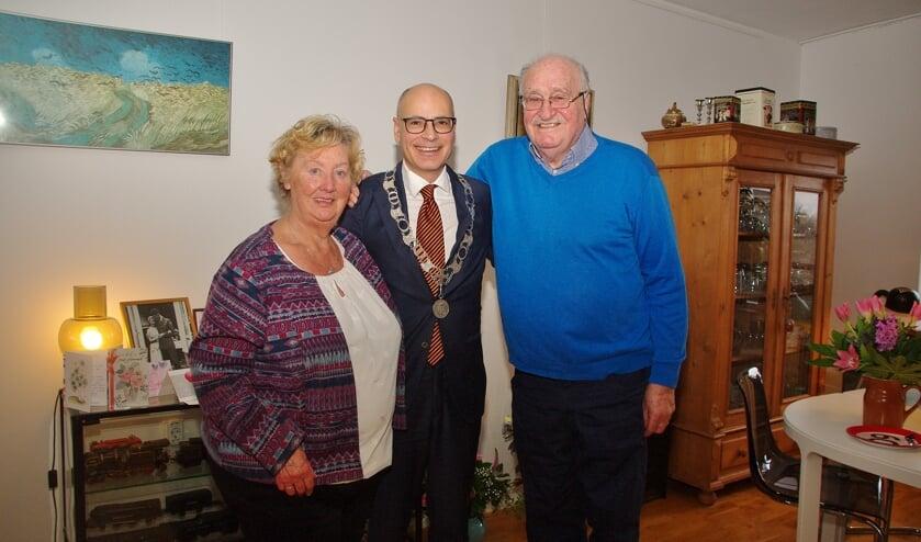 Bruidspaar Anneke en Frits de Winter met de burgemeester in hun midden. | Foto Willemien Timmers