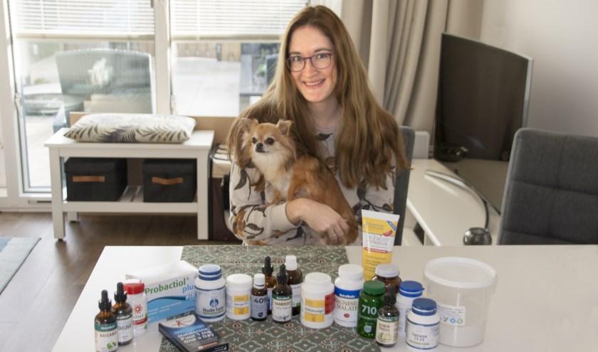 Mariëlle met haar hondje Benthe, te midden van alle supplementen die ze nodig heeft.