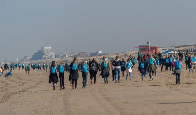 De kinderen wandelen deels over strand.