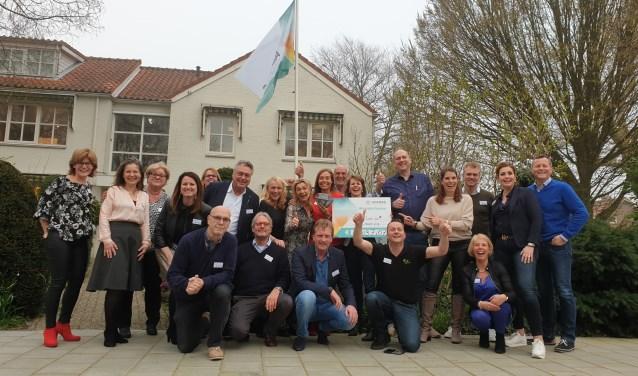 Trotse gezichten bij de deelnemers. Annelies Osinga (met bord) en voorzitter Arthur van Dijk (rechts) zijn blij met het enorme bedrag.