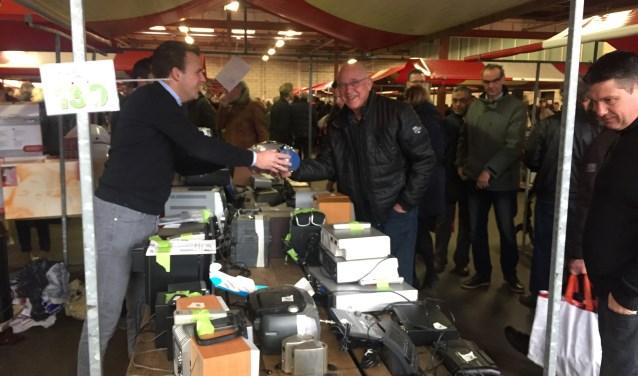 Een tevreden bezoeker doet een goede koop bij een van de vele kramen van de snuffelmarkt.