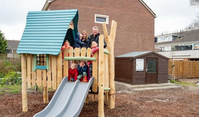 Bestuursleden Jeanine van Jaarsveld en Albert Verkuyl van buurtverenigingen Op Dreef met een aantal buurtkinderen op het nieuwe speelhuisje. | Foto: J.P. Kranenburg