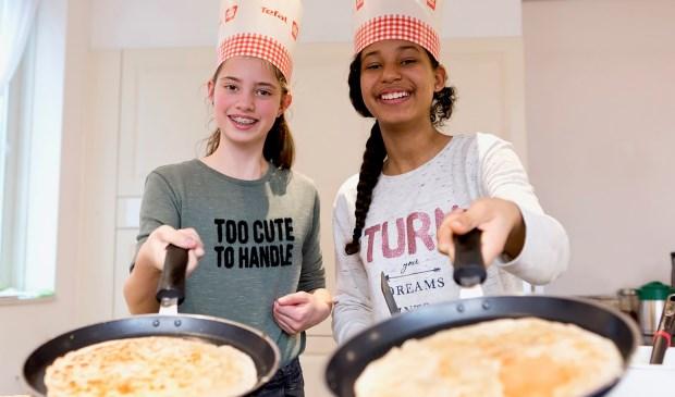 Leerlingen bakken pannenkoeken voor ouderen en genieten zo van een gezellig samenzijn.