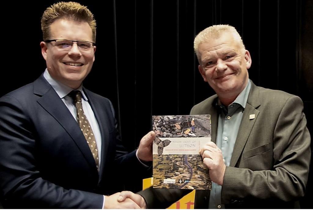 Menno Dijkstra (links) overhandigt het eerste exemplaar van het publieksboekje 'Nieuw Licht op Leython' aan wethouder Daan Binnendijk. Foto: J.P.Kranenburg © uitgeverij Verhagen