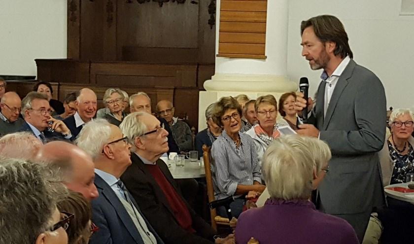 Moderator Huibrecht Bos tijdens een eerder debat in gesprek met een deelnemer.