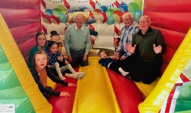 Opa Club bestuursleden Simon Brandt en Helmut Fellner en lid Joop Mensch hebben dit fantastische cadeau in het KDC in gebruik gesteld. Samen met de kinderen hadden zij veel plezier op het veelkleurige springkussen.