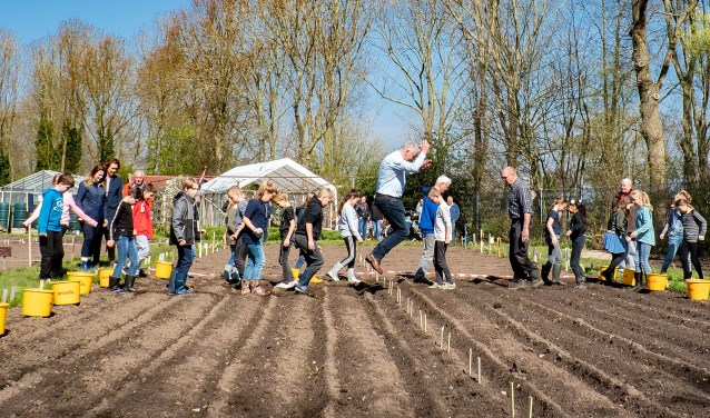 Wethouder Daan Binnendijk maakt een enthousiaste sprong terwijl hij de kinderen van de Leeuwerik voorgaat bij het paadjestrappen.