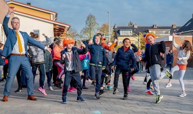 Op KBS De Schakel werden de Koningsspelen geopend met het dansen en zingen van de Pasapas. Ook wethouder Willem Joosten van onderwijs en sport (geheel links) deed mee.