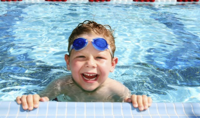 Smiling six year old boy in a sunny swimming pool