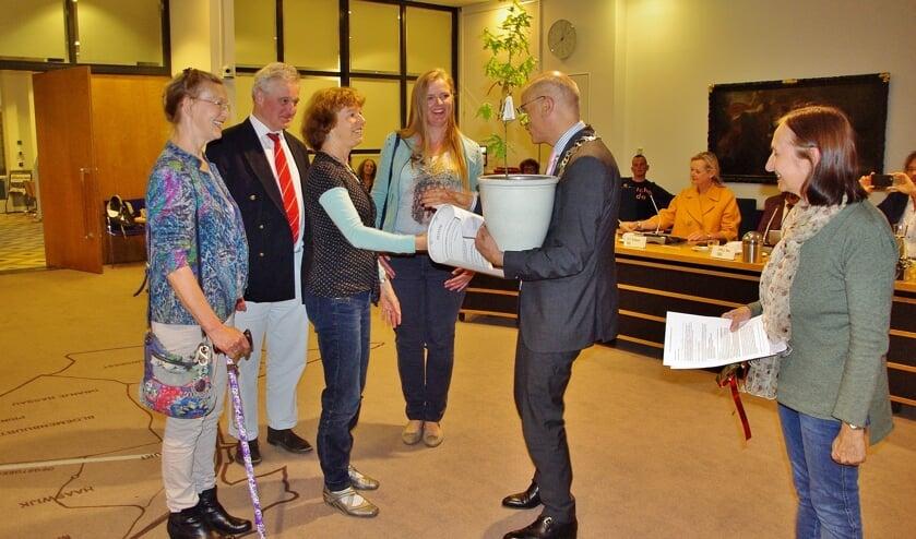 Burgemeester Jaensch kreeg de handtekeningen en een jonge zomereik aangeboden aan het begin van de raadsvergadering.