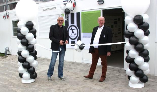Met naast hem voorzitter Meijvogel knipt wethouder sportzaken Sjaak van den Berg het lint door bij de tijdelijke huisvesting van SJC. | Foto: Wim Siemerink