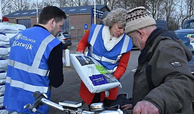 De wethouders Van Starkenburg en Salman deelden zakken compost uit. | Foto: Piet van Kampen