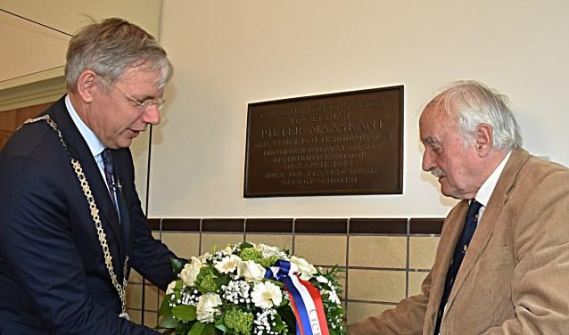 Neef Pieter Maaskant legt samen met burgemeester Cornelis Visser een bloemstuk bij de plaquette.   Foto en tekst: Piet van Kampen