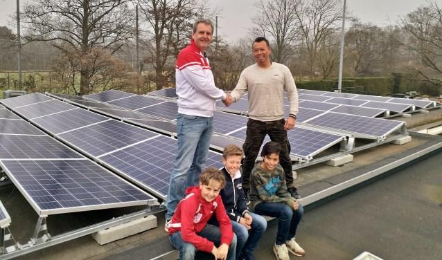 Erwin Gosenson van Solar Group draagt de zonnepaneleninstallatie over aan de voorzitter van OLTC Dick de Groot in het bijzijn van drie jeugdleden.