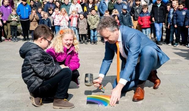 Samen met twee leerlingen legt wethouder Willem Joosten de laatste steen in het vernieuwde plein van PCOB De Regenboog.