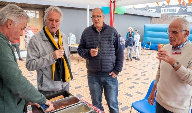 Bestuursleden Robert Laan (tweede van links) en Jaap Timmermans (geheel rechts) genieten van een ijsje op het verjaarsfeest van \t Buurthuis.   Foto: J.P. Kranenburg