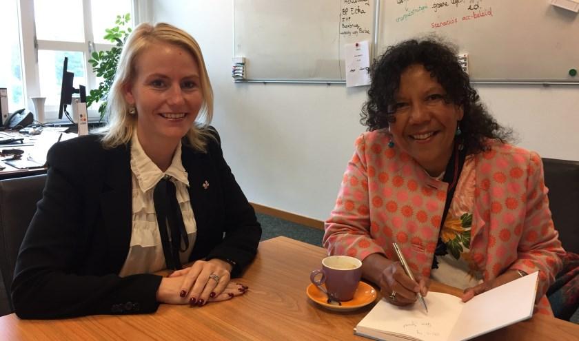 Wethouder Van der Laan neemt het boek van Helen Workala in ontvangst.