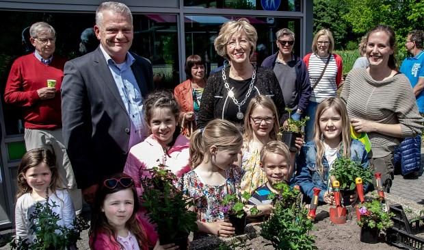 Wethouder Daan Binnendijk, burgemeester Laila Driessen en MEC medewerkster Marieke Weishaupt met een aantal jonge natuurliefhebbers bij de  plantenbak, waarin vlak voor de opening de laatste plantjes gezet werden.
