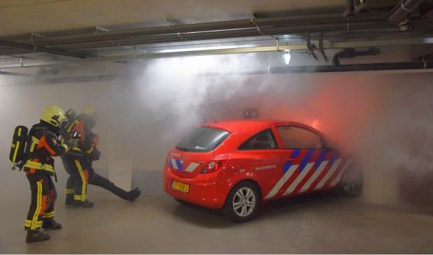 De brandweer redt een 'slachtoffer' bij de brandweeroefening in de parkeergarage van De Ommedijk.