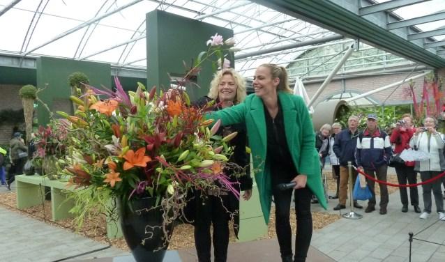 Nicolette Kluijver (rechts) steekt een lelietak in een bloemstuk, daarbij bijgestaan door Stephanie van Erven.