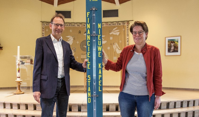 Gert Binnendijk en Astrid Buskermolen bij de thermometer, waarop de stand wordt bijgehouden. | Foto: Adrie van Duijvenvoorde