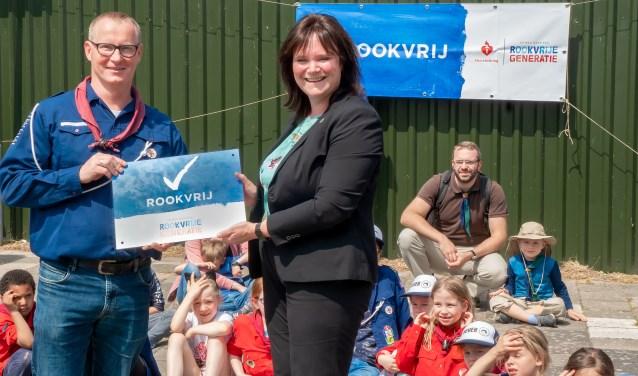 Wethouder Angelique Beekhuizen overhandigt het bord 'Rookvrij' aan voorzitter Bas van den Berg van de scoutingvereniging.