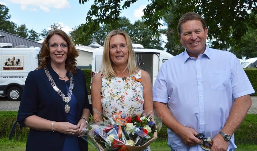 Burgemeester Carla Breuer verrast Annemarie van den Brink met een lintje. Ook man Gilbert is trots. | Foto: pr.