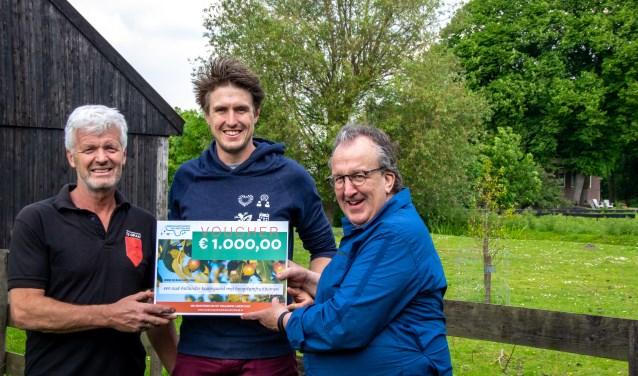 Peter van den Akker overhandigt de cheque van het Landschapsfond aan vader en zoon De Graaf.