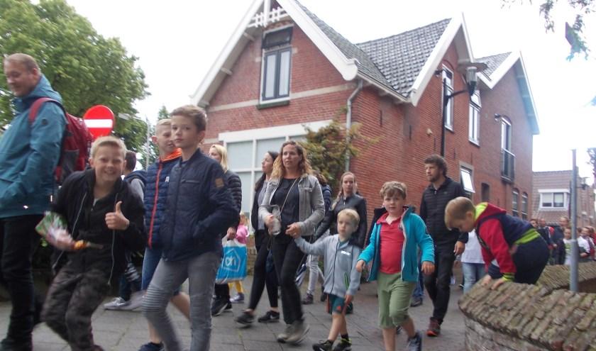 De deelnemers met hun begeleiders wurmen zich door het Schoollaantje.   Foto:  Piet de Boer.