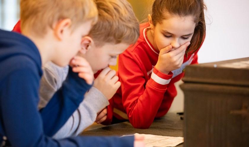 Kinderen spelen de omgekeerde escape room in de bibliotheek. | Foto: pr.
