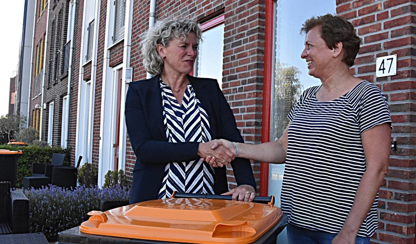 Mevrouw Van den Oever neemt de container van wethouder Corien van Starkenburg in ontvangst.