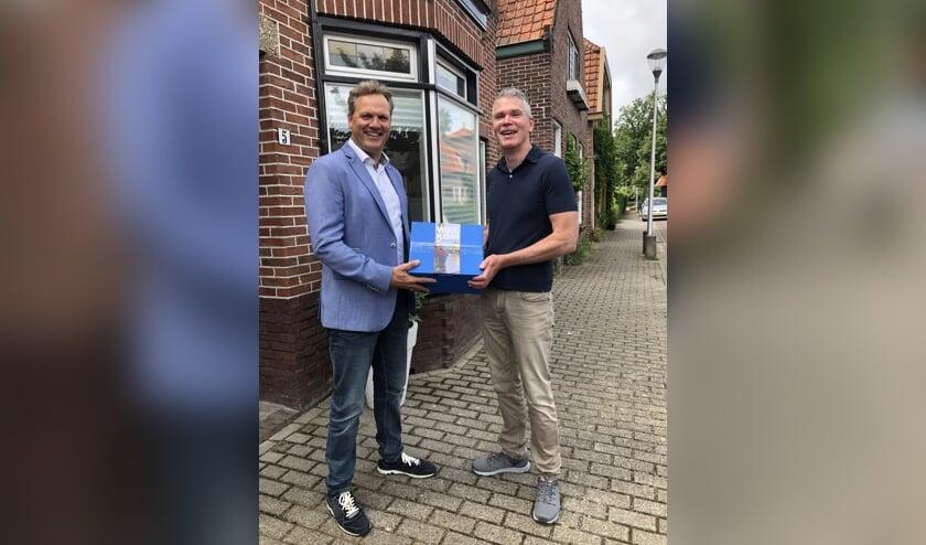 Arjan Heijl overhandigt het eerste welkomstpakket aan Erik van Gogh. Hij woont sinds juni in de Warmundastraat.  Foto: pr.