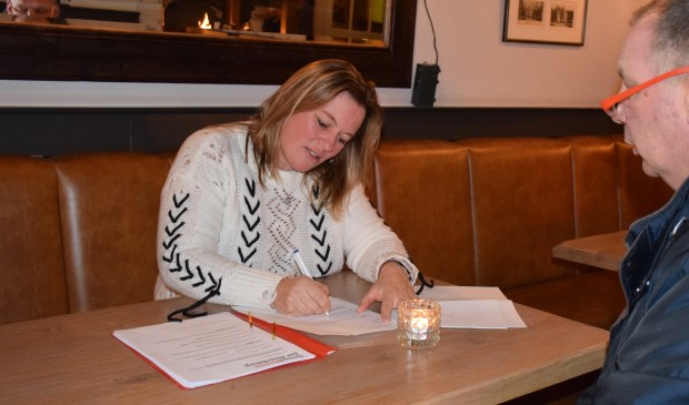 Sandra Konings, van autorijschool Konings in Apeldoorn, is voorzitter van het broodfonds. Hier tekent zij een van de contracten.