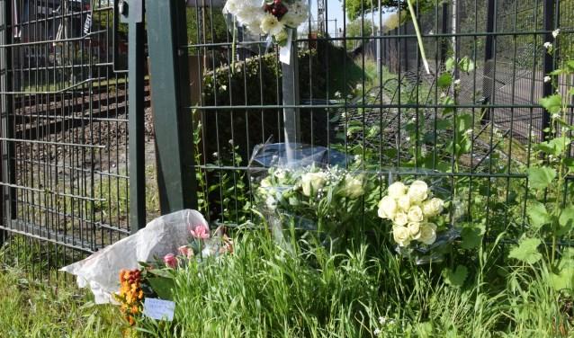 Op de spoorwegovergang hebben verschillende mensen bloemen gelegd als eerbetoon aan Henk Reinink.