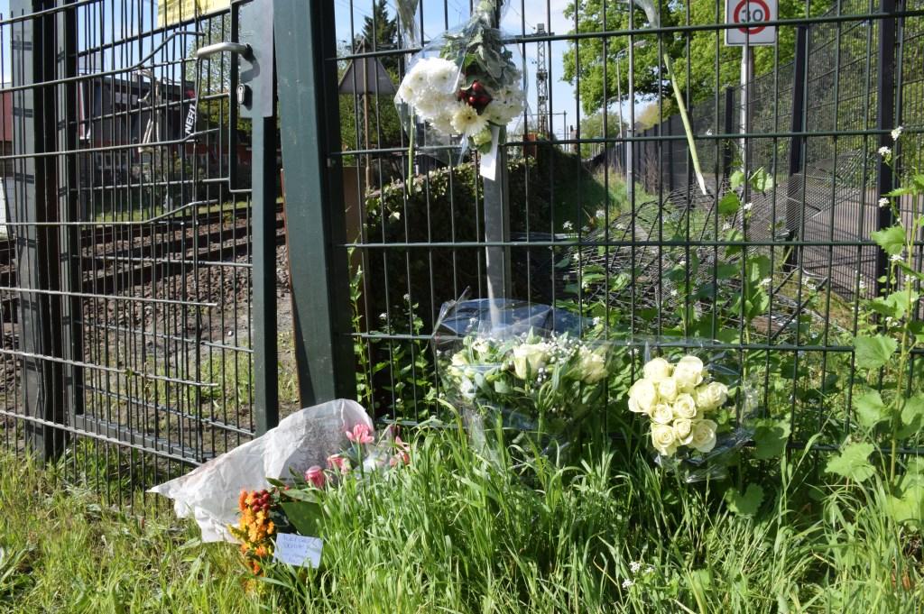 Bij de spoorwegovergang hebben verschillende mensen bloemen gelegd als eerbetoon aan Henk Reinink.  © rij-instructie.nl