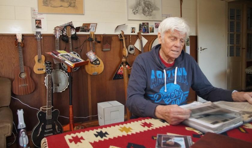 Temidden van zijn muziekinstrumenten bladert Ruud door zijn map met gedichten (Foto, Cor Delissen)