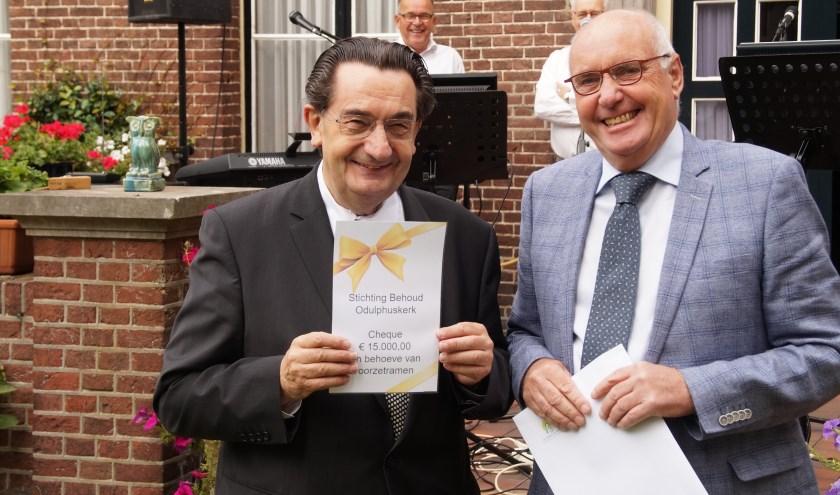 Pastoor Brouwers is zeer verguld met de cheque, overhandigd door Gerard Govers (Foto, Cor Delissen)