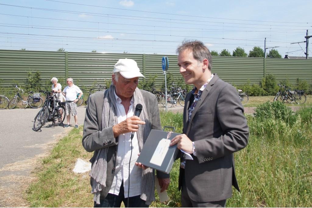 Auke de Vries draagt de 'eigendomspapieren'  over aan wethouder Stan van der Heijden (Foto, Cor Delissen)  © Groeiend Best