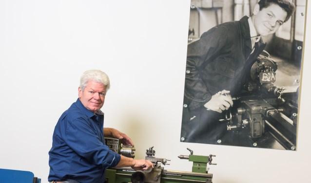 Wim van Roy in zijn atelier bij een draaibank waar hij op de foto achter hem als jongen van 12 jaar voor het eerst kennis maakte met zijn vak