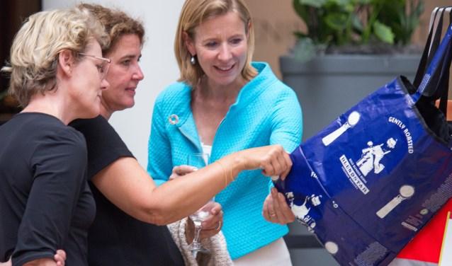 Ellen Willink (m) laat curator Leonne Cuppen  van Yksi Expo (l) en staatssecretaris Stientje van Veldhoven van Infrastructuur en Waterstaat (r) één van haar tassen zien tijdens de opening van de expositie in San Francisco. Foto: Ion Baaijens