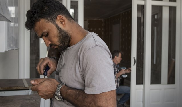 Hasan Alkasas uit Syrie en aannemer op de achtergrond Peter de Groot aan het werk in de Drie Mollen. Foto: Michel van  den Langenberg