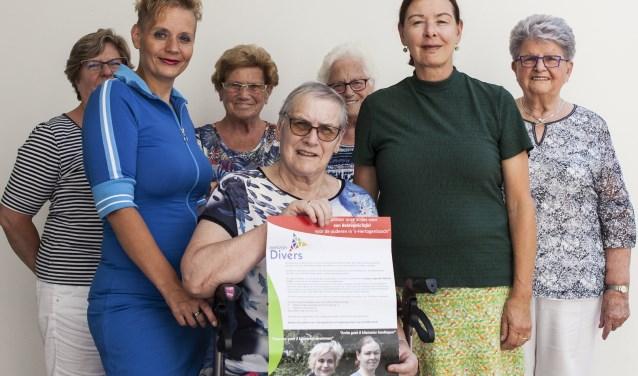 Susanne (tweede van links) en Anita (tweede van rechts) samen met een aantal bezoekers en vrijwilligers van de huiskamers. Foto: Michel van de Langenberg.