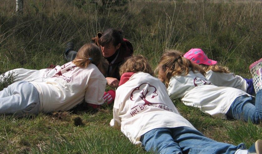 Vol concentratie kijken de kinderen met hun wachter naar kriebelbeestjes en nog veel meer ander moois.