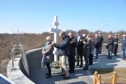 Belangstellenden en nabestaanden lopen langs het kruis op de gedenkplaats.