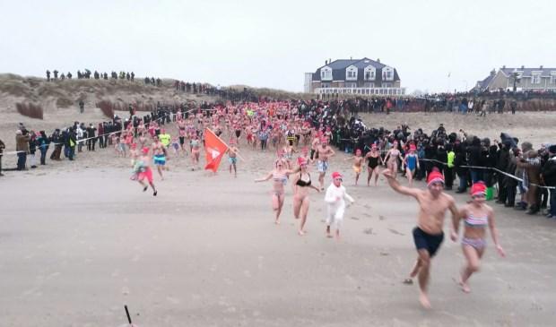 Nieuwjaarduikers rennen in De Koog naar zee.  (Foto Job Schepers)