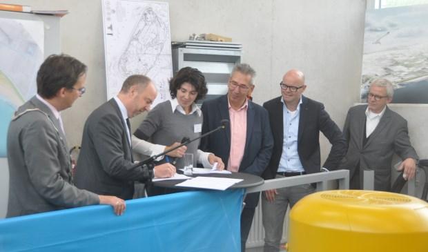 Francis Verhees, directeur Baggerwerken Benelux van Jan De Nul zet zijn handtekening voor de aanleg van de zandige PH-dijk.
