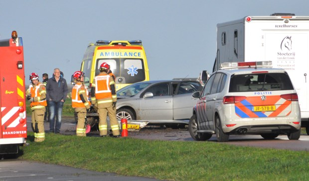 Hulpverleners bij de beschadigde auto.