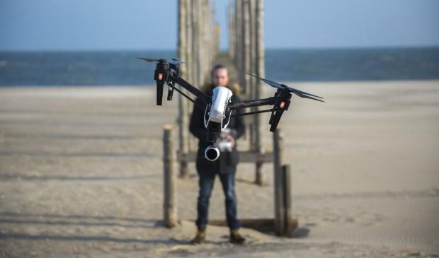 Gerhard Smit met een drone waar een camera aan hangt.