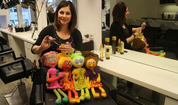 De poppen van Janneke Goënga in de stoel bij kapster Iris Baas.